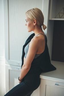 Donna caucasica con capelli biondi che indossa abbigliamento sportivo in posa a casa