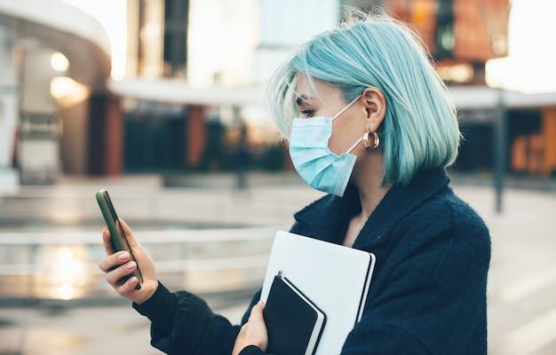 La donna caucasica con i capelli blu sta chattando con qualcuno mentre indossa una maschera protettiva e tiene un computer all'esterno