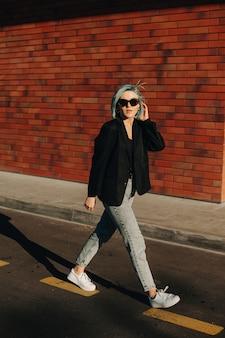Donna caucasica con capelli blu che cammina per strada e guardando al tramonto attraverso gli occhiali