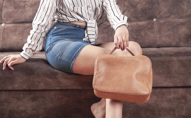 Donna caucasica con una borsa marrone a casa.