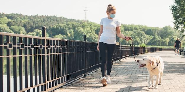 La donna caucasica con la mascherina medica sul viso sta camminando con il suo cane vicino a un lago nel parco durante una calda giornata estiva