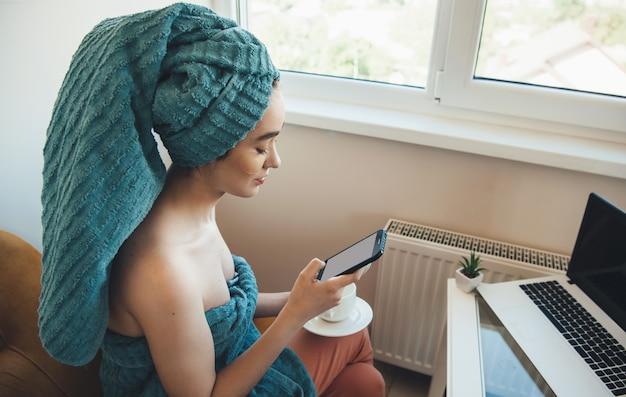 La donna caucasica con un asciugamano sulla testa sta chattando sul cellulare e sul laptop a casa dopo il bagno