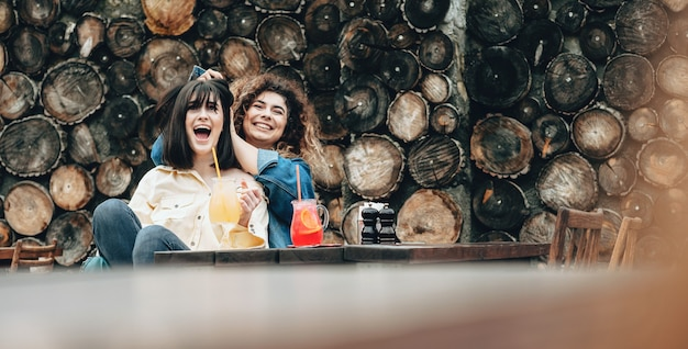 Le donne caucasiche che bevono cocktail fuori su una parete di legno stanno giocando insieme