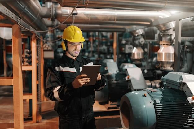 Lavoratore caucasico nella pianta dell'industria pesante con il casco e in uniforme facendo uso della compressa per lavoro.