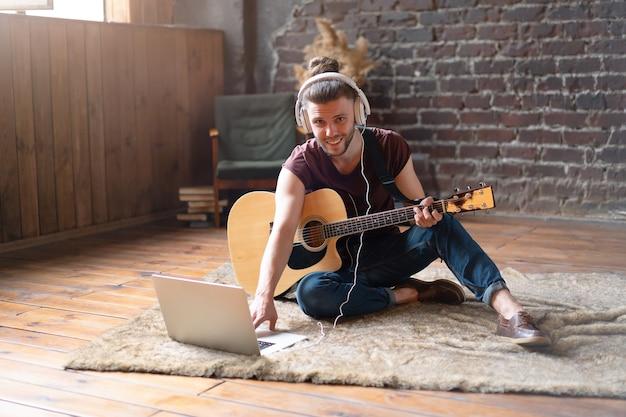 Giovani adulti caucasici che imparano la lezione di musica online con la chitarra con il dispositivo mobile del computer dell'insegnante distante. uomo bello hipster che insegna musica attraverso il computer portatile, concetto di apprendimento dell'istruzione a distanza