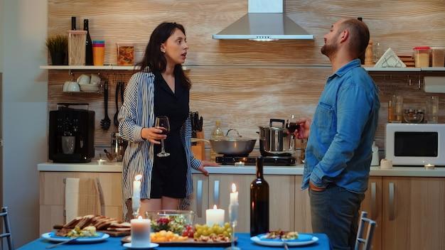 Giovani adulti caucasici che combattono durante la cena romantica. persone frustrate con problemi di coppia che hanno conflitti a casa, in cucina, bevono vino rosso, parlano, dopo aver mangiato nella sala da pranzo