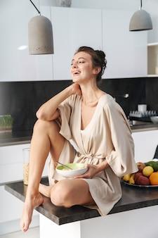 Caucasica giovane bella donna in abiti per il tempo libero facendo colazione con muesli e latte a casa