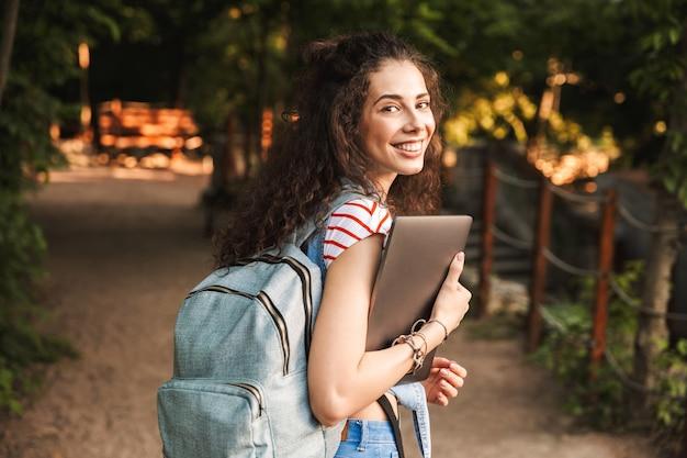 Indoeuropea giovane donna bruna indossando uno zaino, camminando attraverso il parco verde con laptop d'argento nelle mani
