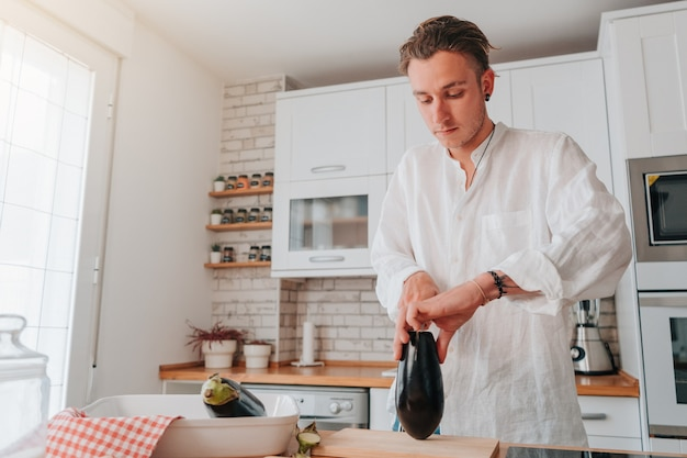 Cuoco giovane caucasico a casa. sta per tagliare la melanzana per iniziare a cucinarla