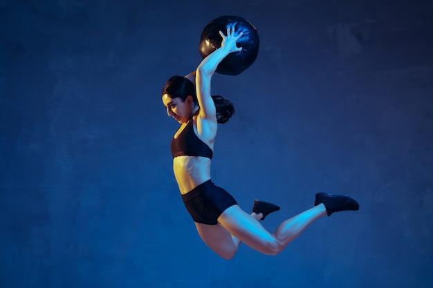 Caucasica giovane atleta femminile che pratica su sfondo blu studio in luce al neon. modello sportivo in volo, salto con palla, allenamento. body building, stile di vita sano, concetto di bellezza e azione.
