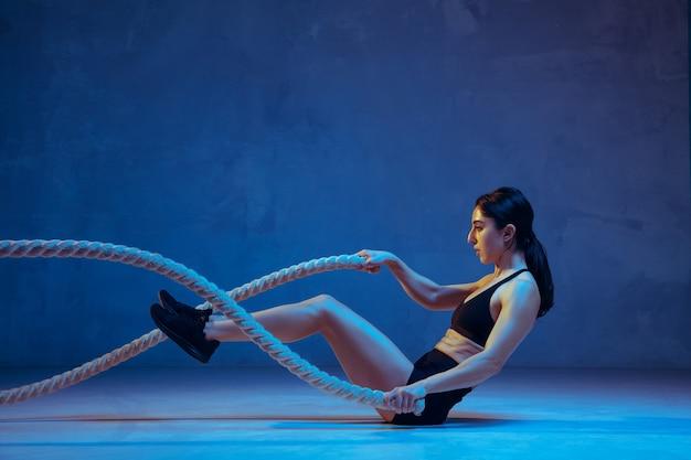 Caucasica giovane atleta femminile che pratica su sfondo blu studio in luce al neon