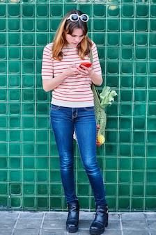 Ragazza giovane caucasica guardando il suo telefono cellulare con una borsa a rete sulla spalla con verdure su un muro verde in strada