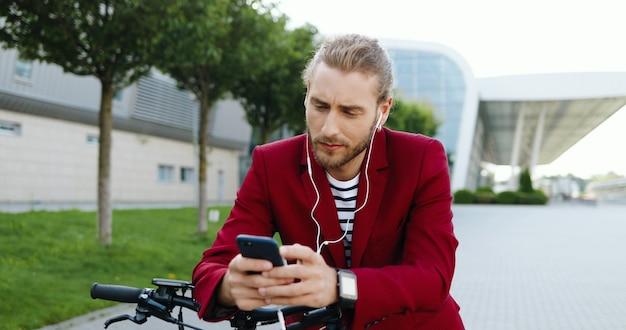 Caucasica giovane uomo bello in giacca rossa in piedi sulla strada a scooter elettrico e ascoltare musica sul telefono cellulare. ragazzo alla moda toccando smartphone in cuffia. messaggio di testo sul cellulare.