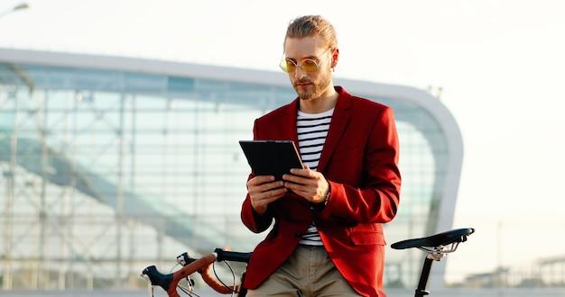 Caucasica giovane uomo bello in piedi in bicicletta e utilizzando il dispositivo tablet. ragazzo alla moda in giacca rossa e occhiali da sole che si appoggia sulla bici e toccando o scorrendo sul gadget del computer in un moderno edificio in vetro.