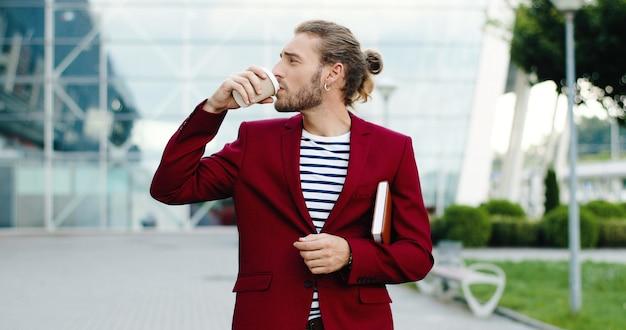 Caucasica giovane imprenditore elegante bello camminare all'aperto in città con pianificatore e sorseggiando drink. edificio moderno del centro affari sullo sfondo. uomo che passeggia e beve caffè da asporto.