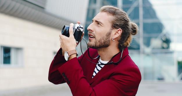 Giovane fotografo maschio alla moda bello caucasico che cattura le immagini con la macchina fotografica della foto all'aperto nella città di affari. sorrise allegro uomo che fa foto di architettura urbana della città.