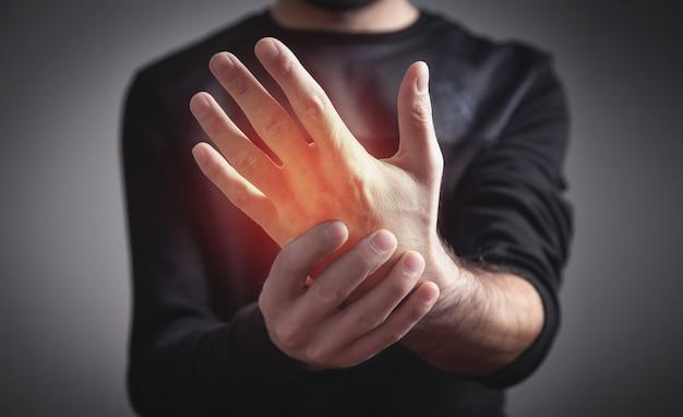 Giovane caucasico che ha dolore in mano.