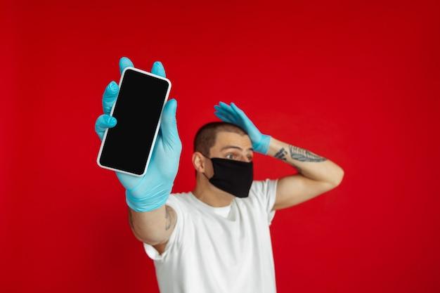 Il giovane caucasico in maschera protettiva e guanti medici sulla parete rossa dello studio mostra lo schermo del telefono in bianco