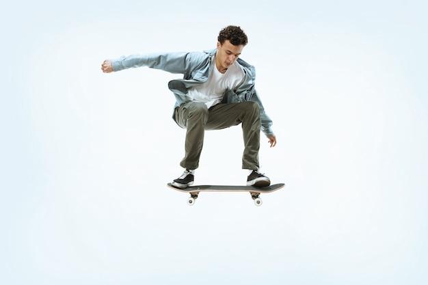 Giovane guidatore di skateboard caucasico in sella isolato su uno sfondo bianco