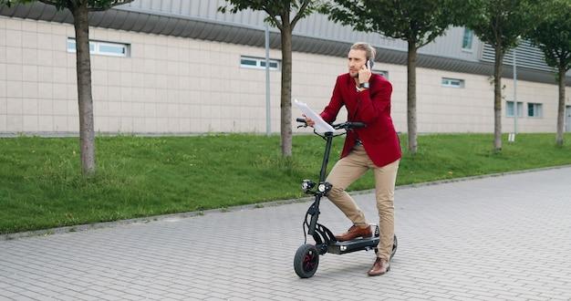 Caucasica giovane imprenditore elegante in piedi al scooter elettrico, parlando al telefono cellulare e tenendo i documenti. all'aperto. uomo bello che parla sul cellulare e legge il contratto. discutere di affari.