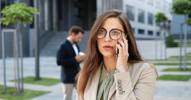Caucasica giovane imprenditrice elegante in bicchieri parlando al cellulare in strada. bella donna che parla sul telefono cellulare all'aperto. donna attraente in occhiali che hanno telefonata. conversazione.
