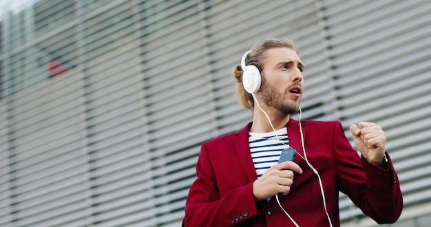Uomo bello alla moda giovane caucasico in cuffie che ascolta la musica su smartphone e canto. all'aperto. allegro bell'aspetto buffo in giacca rossa canta e ascolta la canzone. lettore di telefoni cellulari.