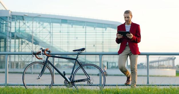 Caucasica giovane uomo bello alla moda in piedi in strada con la bici, videochattare sul dispositivo tablet. maschio che parla tramite webcam online su computer gadget con bicicletta all'esterno. videochatting parlando.