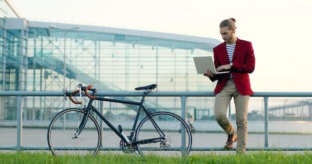 Caucasica giovane elegante uomo bello in piedi in strada con la bici, lavorando su un computer portatile e digitando sulla tastiera. libero professionista maschio lavora con la bicicletta all'esterno. libero professionista.