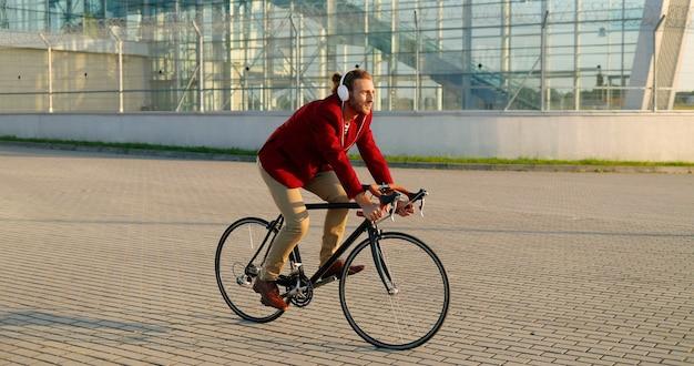 Ciclista maschio alla moda giovane caucasico in giacca casual rossa e cuffie in sella a una bicicletta in strada in città. bell'uomo con giro in bicicletta e ascolto di musica. panorama della città. al di fuori.