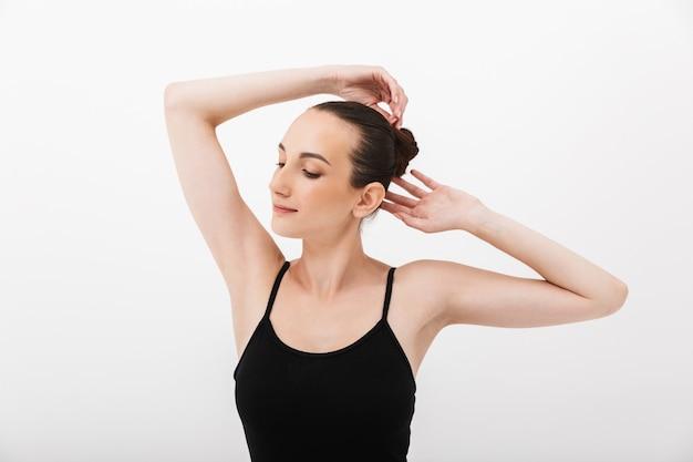 Ballerina caucasica della giovane donna che pratica e allunga il suo corpo isolato sopra il fondo bianco della parete
