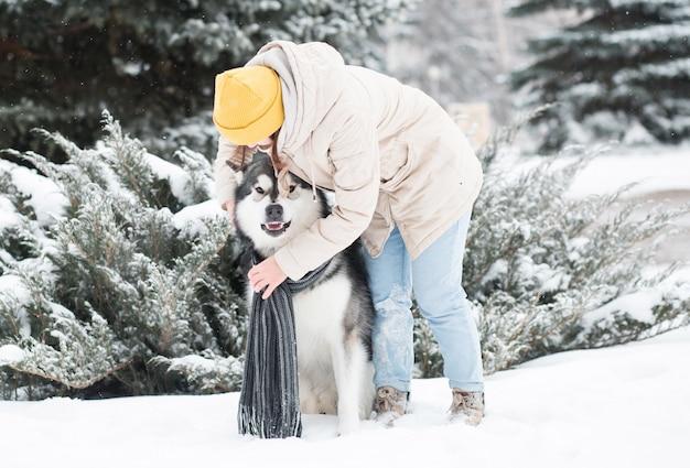 Sciarpa caucasica del vestito dalla giovane donna alaskan malamute cane nella foresta di inverno. avvicinamento.