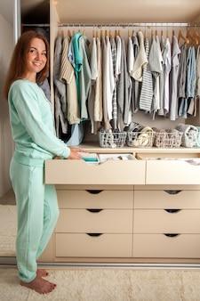 Casalinga caucasica della giovane donna che tiene il contenitore con i calzini, le mutandine e la biancheria intima. deposito di vestiti.