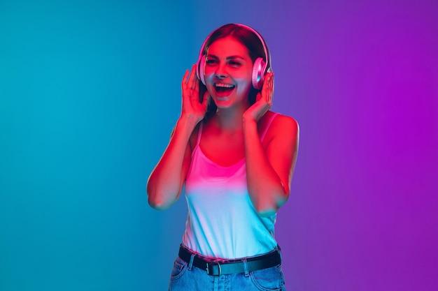 Ritratto di giovane donna caucasica isolato su sfondo viola-blu sfumato in luce al neon
