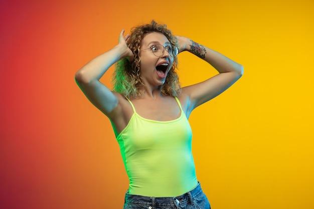 Ritratto di giovane donna caucasica isolato su sfondo sfumato per studio al neon. bellissimo modello riccio femminile in stile casual. concetto di emozioni umane, espressione facciale, gioventù, vendite, pubblicità.