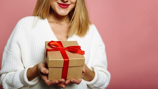 Giovane donna caucasica in cappello della santa che mostra scatola regalo rossa e sorridente isolato su sfondo rosa. felice anno nuovo celebrazione concetto di vacanza allegra. avvicinamento. banner web.