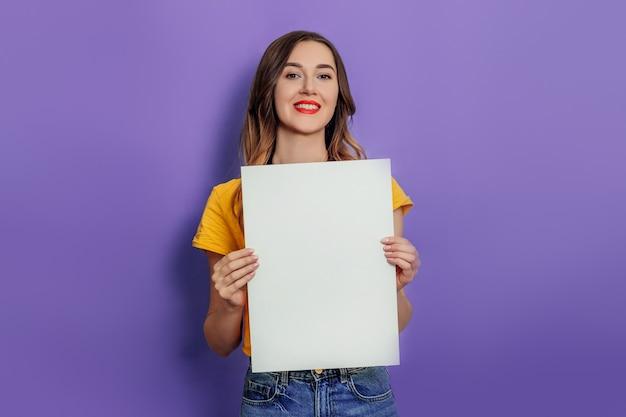 Giovane donna caucasica che sorride e che tiene manifesto in bianco che indossa maglietta gialla isolata sopra fondo lilla in studio. mockup per il design
