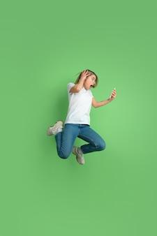 Ritratto di giovane donna caucasica sulla parete verde dello studio?