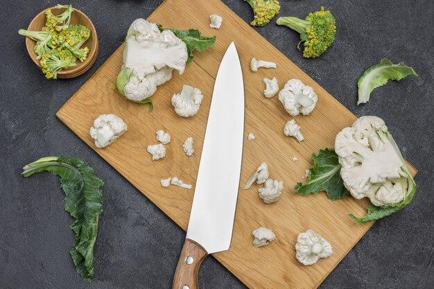 Cavolfiore e coltello da cucina sul tagliere. fondo di legno. lay piatto