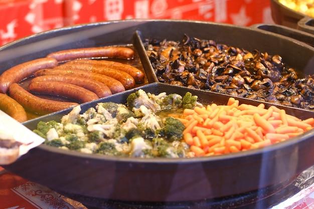 Cavolfiore, funghi, carote, salsicce fritte su una grande padella rotonda in una vetrina di fast food cafe.