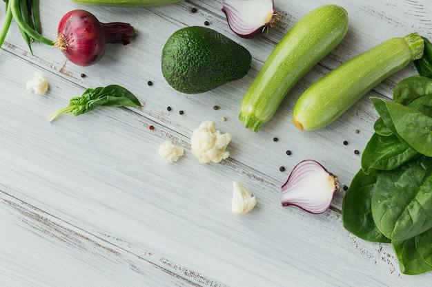 Cavolfiore, zucchine, cipolla rossa, fagiolini, uova, avocado, formaggio e foglie di spinaci sul tavolo di legno bianco
