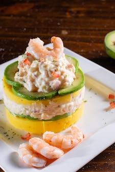 Causa con frutti di mare gamberi cibo tipico peruviano nella tavola di legno