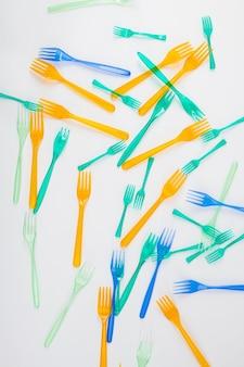 Causando il riscaldamento globale. forchette di plastica pericolose luminose e colorate che colpiscono la natura e sono il risultato di gas serra