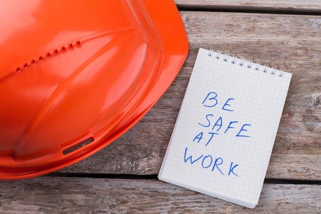Attenzione essere al sicuro sul lavoro. casco protettivo e blocco note del lavoratore sulla tavola di legno invecchiata.