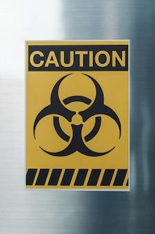 Segno di pericolo attenzione segno di rischio biologico sul congelatore