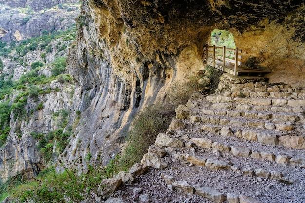 Grotta in montagna con sentiero a gradini per escursionisti.