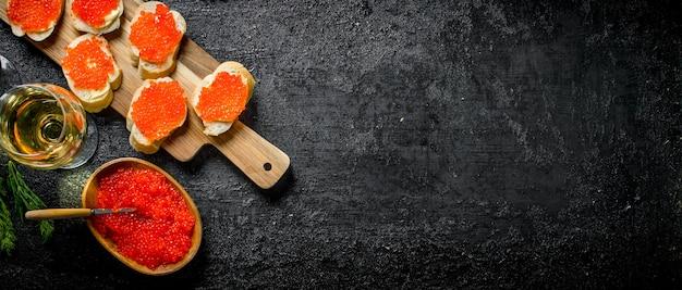 Caviale nella ciotola, panini con caviale rosso e vino. sulla superficie rustica nera