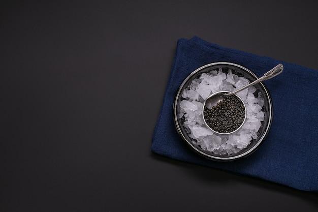 Caviale in una scatola di metallo su sfondo nero