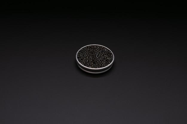 Caviale in una scatola di metallo con spazio per scrivere su nero