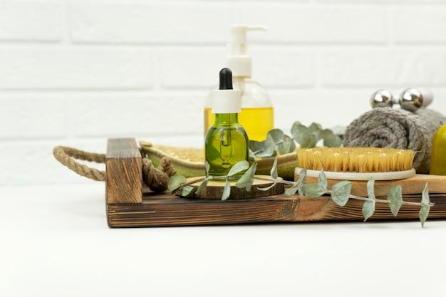 Un olio verde cbd, un rullo per il viso, una spazzola per il massaggio a secco giacciono su un vassoio di legno
