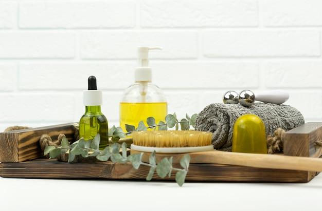 Un olio verde cbd, un rullo per il viso, una spazzola per il massaggio a secco stanno su un vassoio di legno in un bagno